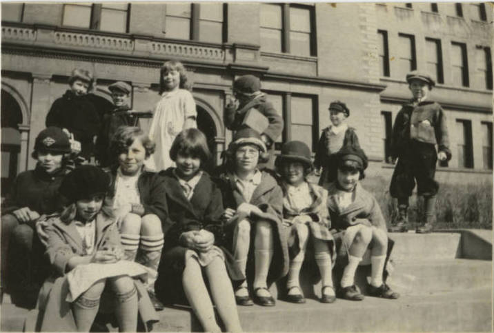 A black and white photo of children in front of a large brick building