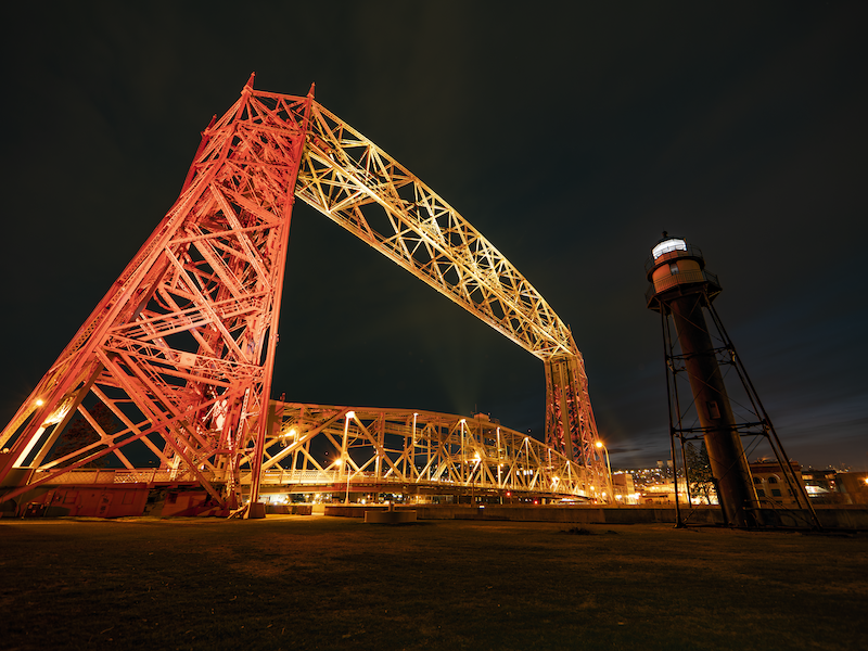 The Duluth Aerial Lift Bridge, lit up at night in maroon and gold.