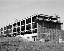 A Black and white photo of a building under construction.