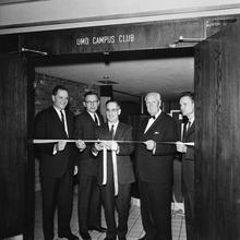 A Black and white photo of five men cutting a ribbon on the UMD Campus Club.