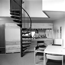 A Black and white photo of a young woman in a studio apartment, looking through an open kitchen, with a spiral staircase visible.